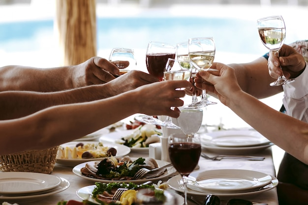 Manos de personas con copas de champán o vino, celebrando y tostado en honor de la boda u otra celebración. Foto gratis