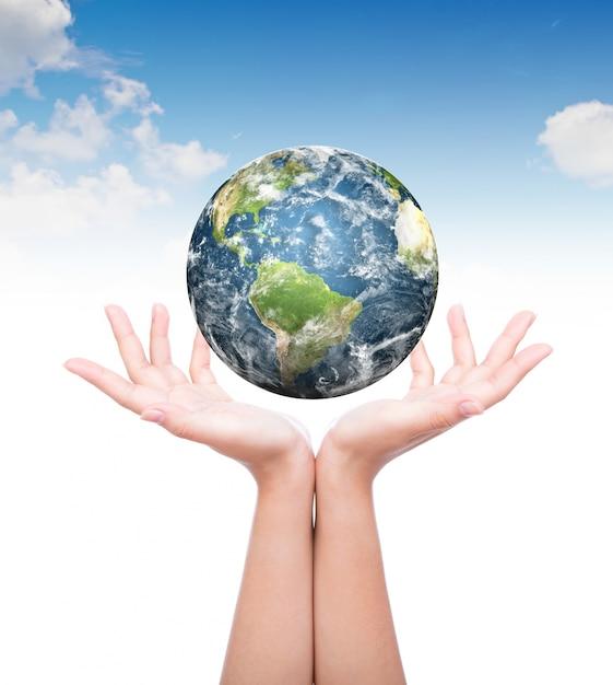Manos con el planeta tierra encima Foto gratis