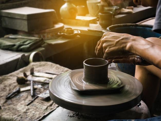 Las manos de potter formando arcilla suave para hacer una olla de barro Foto Premium