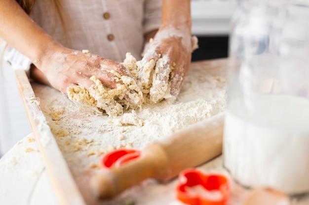 Manos preparando masa junto al rodillo de cocina Foto gratis