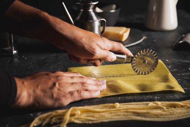 Manos de primer plano con cortador de pizza y utensilios Foto gratis