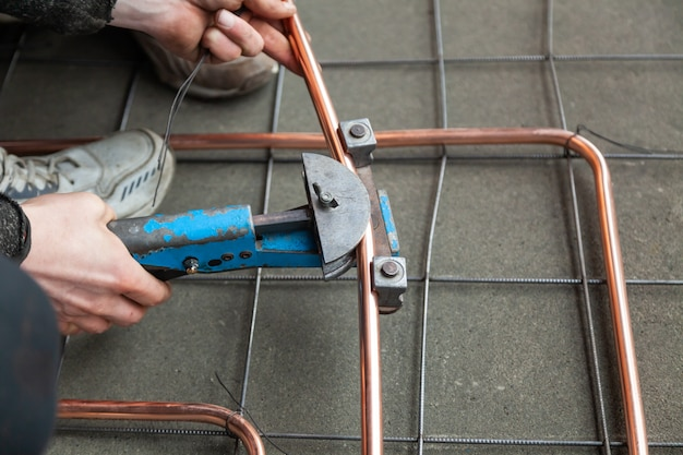 Manos de primer plano dobla tubos de cobre por doblador de tubos Foto Premium