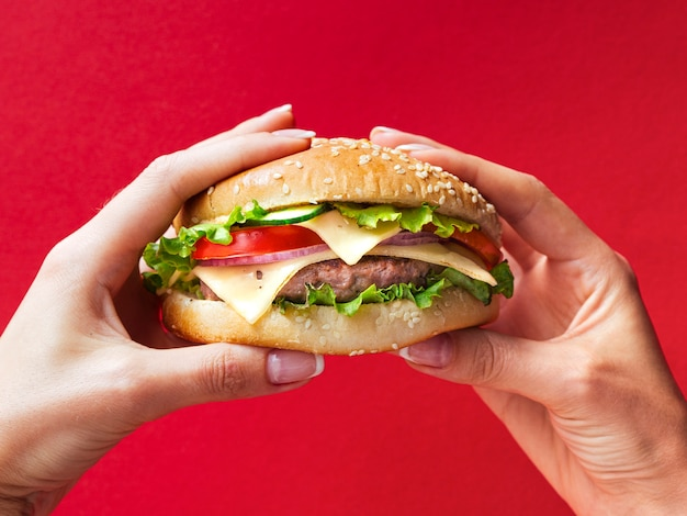 Manos de primer plano con gran hamburguesa con queso Foto gratis