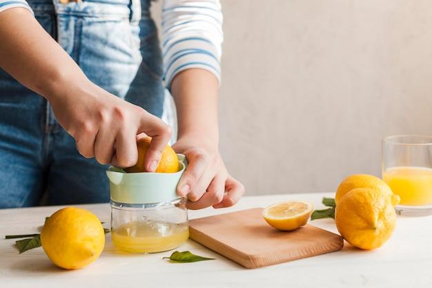 Manos de primer plano haciendo jugo de limón Foto gratis