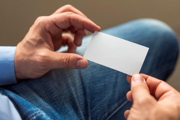 Manos de primer plano con tarjeta blanca Foto gratis