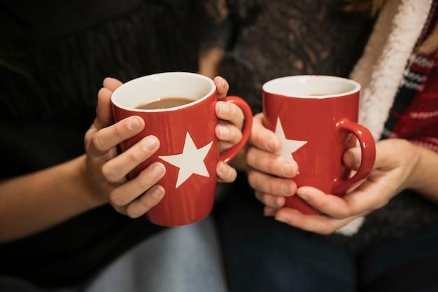 Manos de primer plano con tazas de café Foto gratis