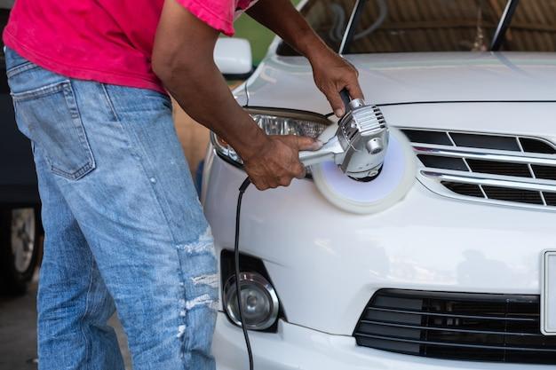 Manos con pulidora orbital pulido coche blanco. detallado del automóvil y concepto de lavado. Foto Premium