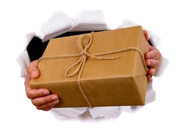 Manos que entregan un paquete a través de fondo de papel rasgado ...