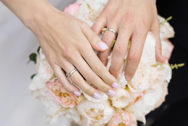 Manos de los recién casados, la novia y el novio, con anillos de boda en un ramo de rosas blancas y de leche y peonías close-up. pareja de boda Foto Premium