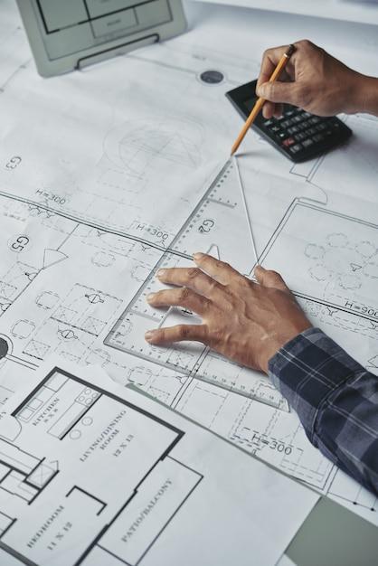 Manos recortadas de planos del arquitecto para el proyecto arquitectónico Foto gratis