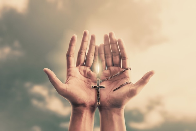 Las manos rezando sostienen un crucifijo o una cruz de collar de metal con fe en la religión y creencia en dios Foto Premium