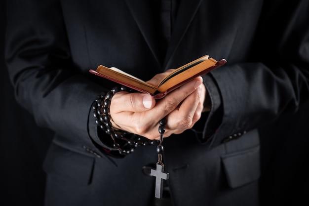 Manos de un sacerdote cristiano vestido de negro con un crucifijo y leyendo el libro del nuevo testamento. persona religiosa estudia la biblia y sostiene cuentas de oración, imagen discreta Foto Premium