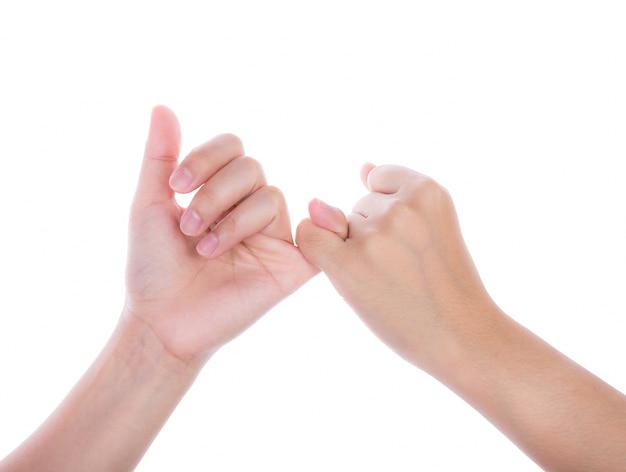 Manos sellando una promesa con los dedos meñiques Foto gratis