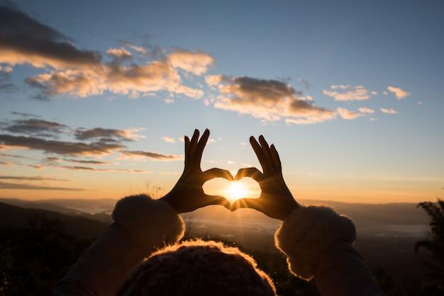 Manos de silueta formando una forma de corazón con la salida del sol Foto gratis