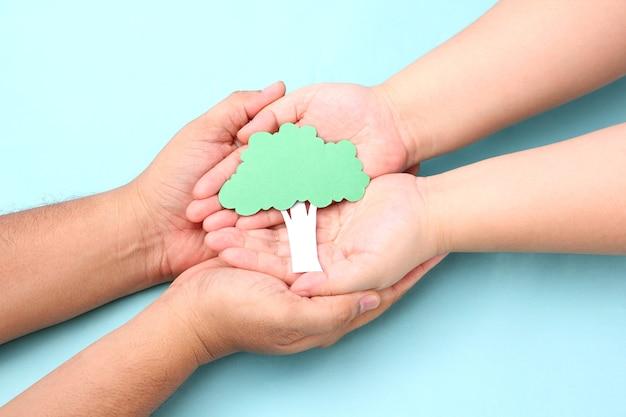 Manos sosteniendo el árbol de papel en azul. Foto Premium