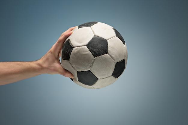 Manos sosteniendo el balón de fútbol Foto gratis