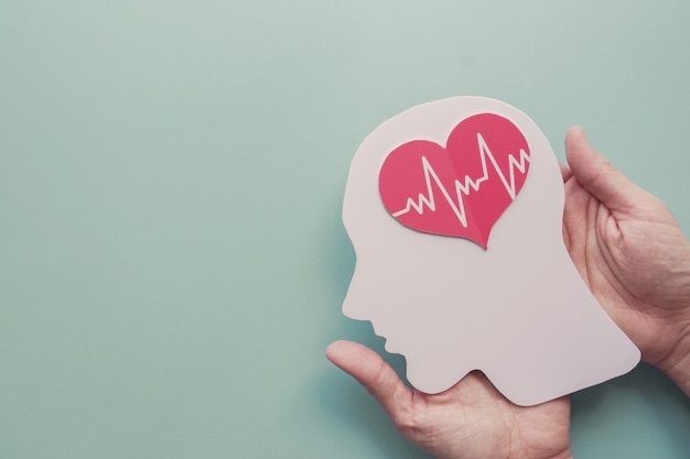 Manos sosteniendo el cerebro y el corazón de papel, día mundial del corazón Foto Premium