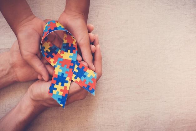 Manos sosteniendo la cinta del rompecabezas para la conciencia del autismo Foto Premium