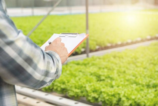 Manos sosteniendo documentos en papel con bolígrafo y escribiendo un informe de notas vegetales orgánicos verdes en vivero Foto Premium