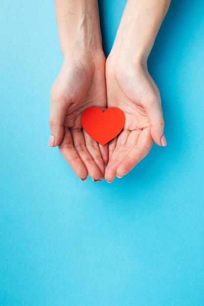 Manos sosteniendo la figura del corazón con espacio de copia Foto gratis