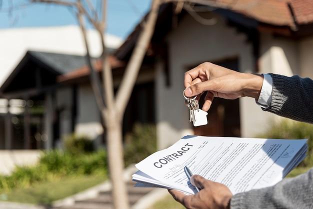Manos sosteniendo llaves de la casa y contrato al aire libre Foto gratis
