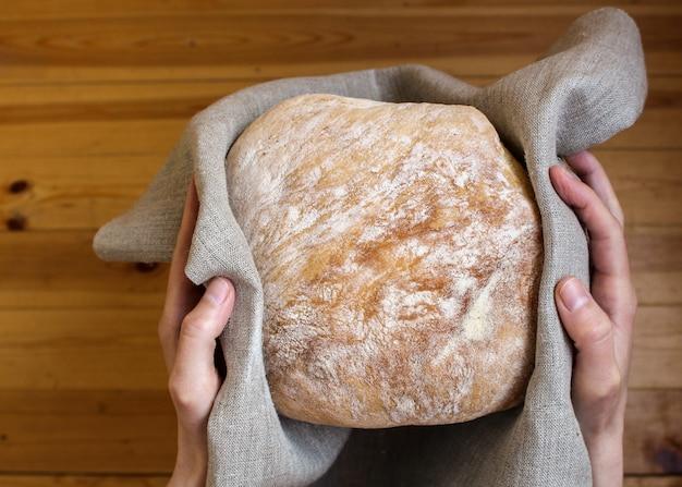 Manos sosteniendo pan recién horneado envuelto en tela de lino. Foto Premium