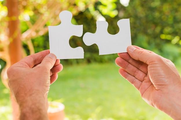 Manos sosteniendo piezas de puzle Foto gratis