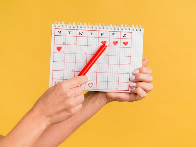 Manos sosteniendo una pluma roja y vista frontal del calendario de época Foto gratis