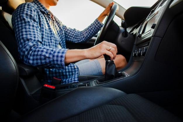 Manos sosteniendo la rueda del coche y la palanca de cambios Foto gratis