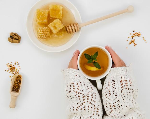 Manos sosteniendo té con miel Foto gratis