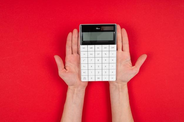 Manos sostiene una calculadora aislada sobre fondo rojo Foto Premium