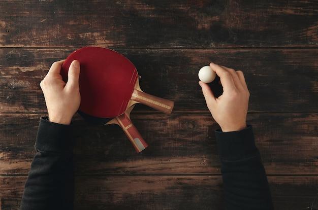 Las manos sostienen dos cohetes de ping pong profesionales, ataque plus y defensa Foto gratis