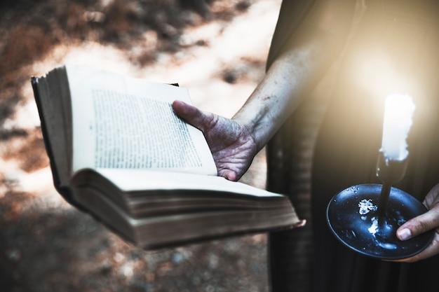 Manos sucias sosteniendo el libro ritual y vela Foto gratis