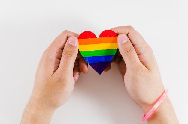 Manos sujetando un corazón con los colores de la bandera del orgullo Foto gratis