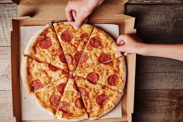 Manos tomando porciones de pizza de una caja de cartón Foto Premium