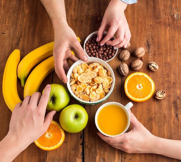 Manos tomando saludable desayuno casero de muesli, manzanas, frutas frescas y nueces Foto gratis