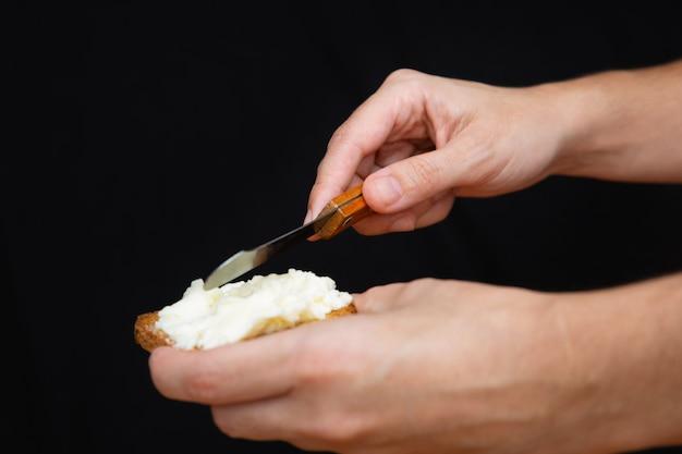 Manos untando queso blando sobre pan tostado Foto gratis
