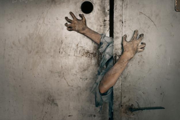 Manos de zombie que sobresalen de la puerta del ascensor Foto Premium