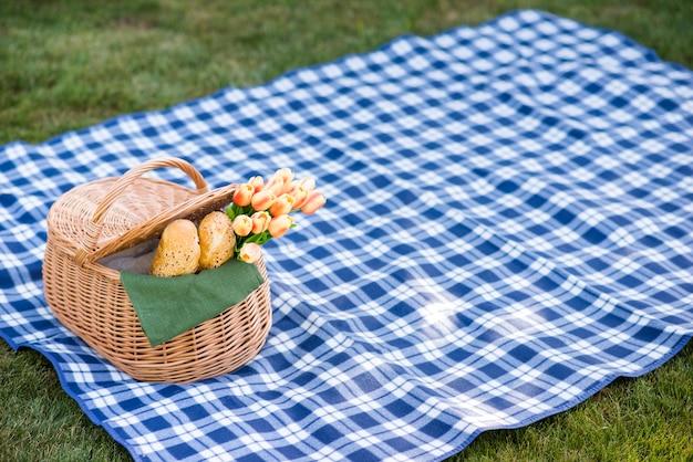 Manta de picnic con una canasta sobre hierba Foto gratis