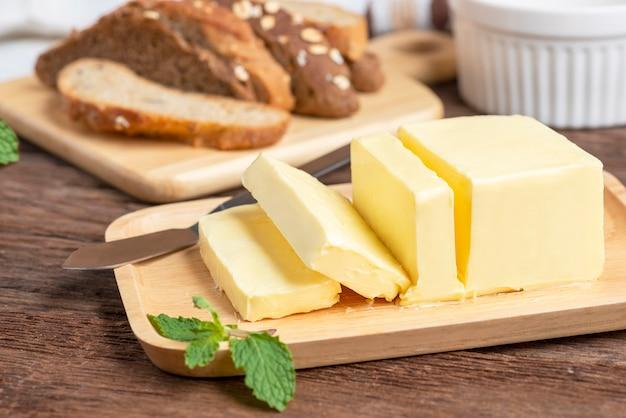 Mantequilla fresca cortada con cuchillo en placa de madera y pan. Foto Premium