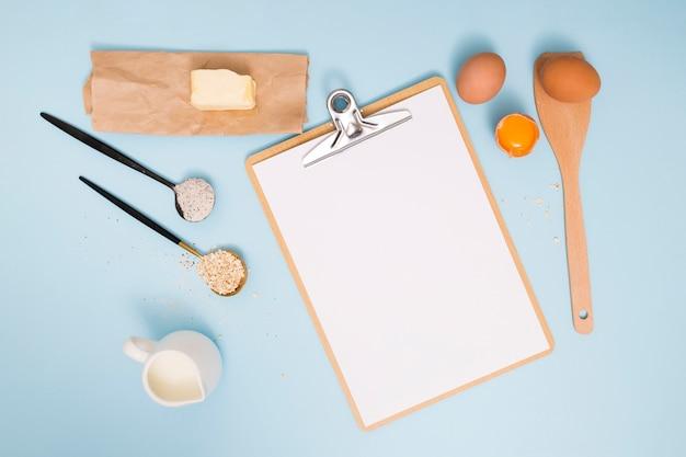 Mantequilla; huevos; harina; salvado de avena y leche con portapapeles sobre fondo azul Foto gratis