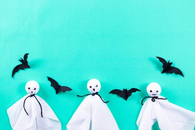 Manualidades de halloween, fantasmas y murciélagos sobre fondo de papel verde pastel. Foto Premium