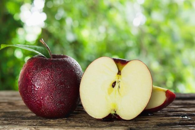 Manzana fresca con gota de agua sobre la piel sobre la naturaleza verde, fruta fresca Foto gratis