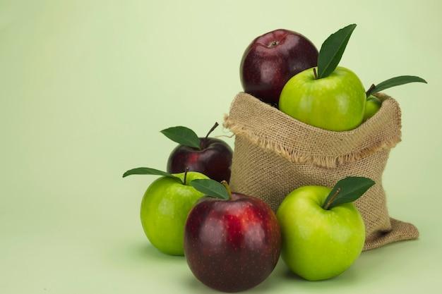 Manzana roja fresca sobre fruta verde suave y fresca Foto gratis