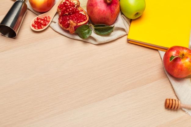 Manzana roja, granada y tarro de miel para el año nuevo judío sobre tabla de madera Foto Premium