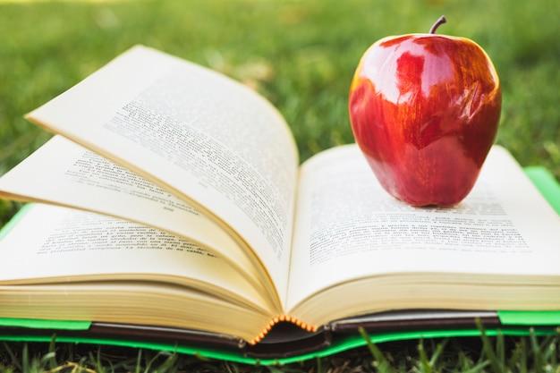 Manzana roja en libro con tapa verde Foto gratis