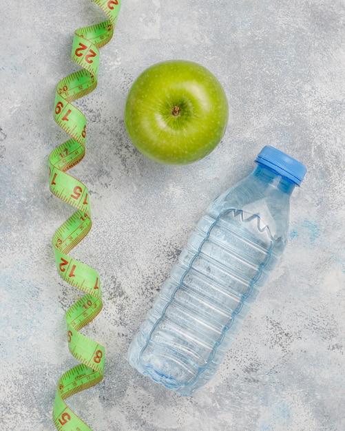 Manzana verde fresca, cinta métrica y botella de agua dulce sobre hormigón gris Foto gratis