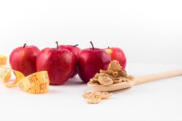 Manzanas con cinta métrica y cereales en cuchara. Foto gratis