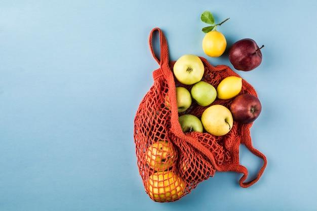 Manzanas y limones en una bolsa de cadena naranja sobre un fondo azul. Foto Premium