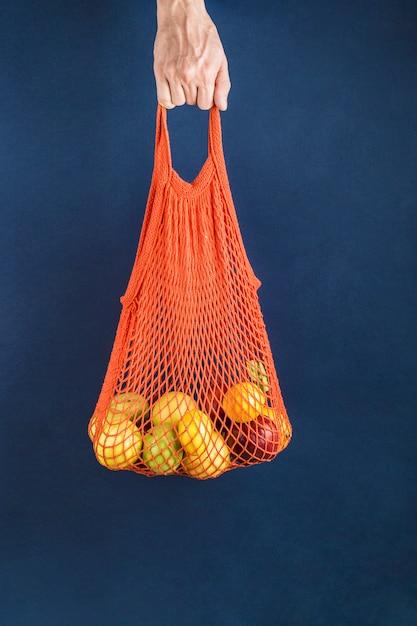 Manzanas y limones en una bolsa naranja en la mano de un hombre Foto Premium